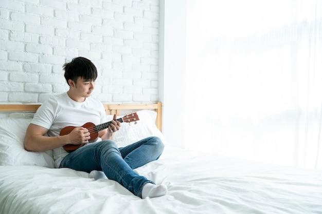 Азиатский красавец сидит на кровати и играет на гитаре укулеле в расслабляющий день дома