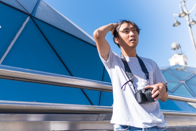 Asian handsome man traveling with a camera
