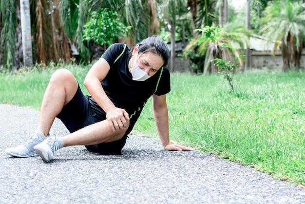 公園で実行中に膝の怪我に苦しんでいるサージカルマスクを身に着けているアジアのハンサムな男