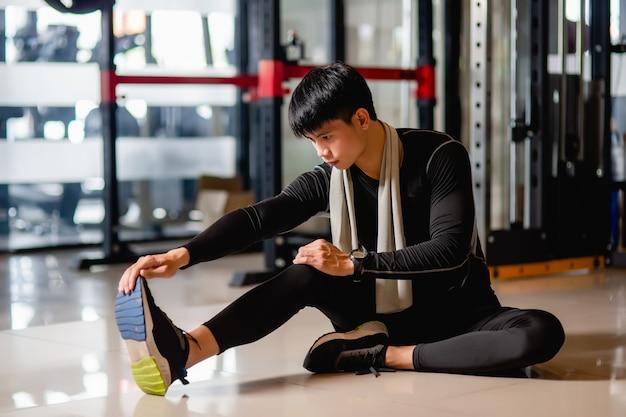 Азиатский красавец в спортивной одежде и умных часах сидит на полу и растягивает мышцы ног перед тренировкой в фитнес-зале,