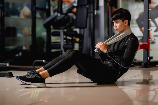 Азиатский красавец в спортивной одежде и умных часах сидит на полу, приседает, чтобы разогреть мышцы перед тренировкой в фитнес-зале,