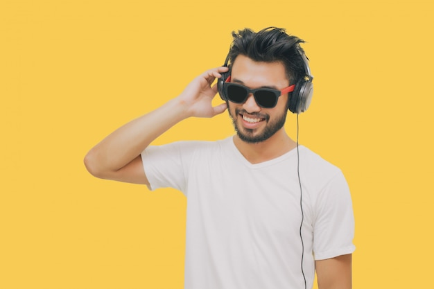 Asian handsome man with a mustache, smiling and laughing and using smart phone to listen music with headphones on yellow background