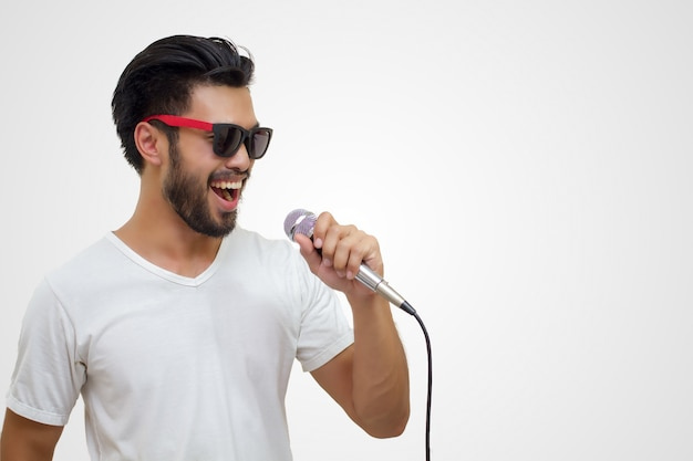 Asian handsome man with a mustache, smiling and singing to the microphone isolated on white backgrou