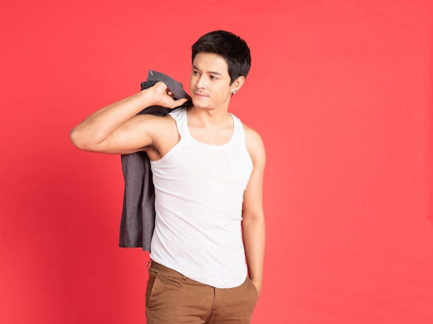 Asian handsome young man with big muscle wearing white vest hand hold take off shirt standing isolated on red wall shot .