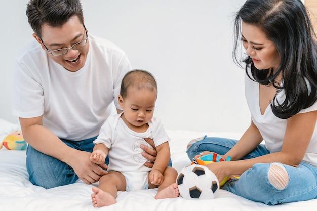 アジアの幸福家族の寝室の父と母親と一緒に赤ちゃんの赤ちゃんの家族のシーン