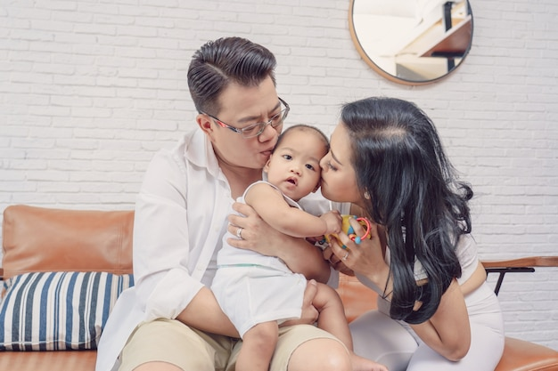 Asian happiness family scene of parent are kissing the boy baby in the living room of hous