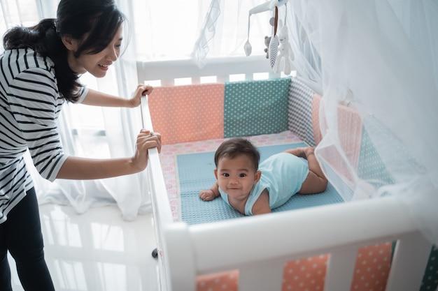 ベビーベッドでアジアの幸せな赤ちゃん