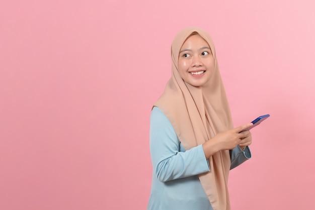 コピースペースとピンク色の背景で隔離のスマートフォンを笑顔で保持しているアジアの幸せな美しい女性。