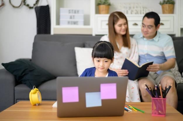 アジアの幸せな娘は、親が自宅のソファに座っている間に、ラップトップを使用してインターネット経由でオンラインで勉強しています。 eラーニングの概念