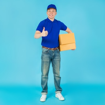 Asian happy delivery man wearing a blue shirt and hat showing thumbs up and carrying paper parcel box.