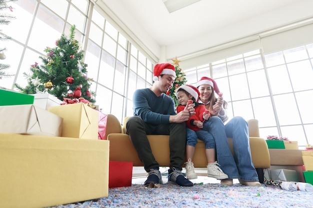아시아의 행복한 가족과 크리스마스를 축하하는 어린 소녀는 거실에 크리스마스 트리가 있는 종이 불꽃놀이와 선물 상자를 당깁니다. 아빠, 엄마, 딸이 산타 모자를 쓰고 집에 소파에 앉아 있습니다.
