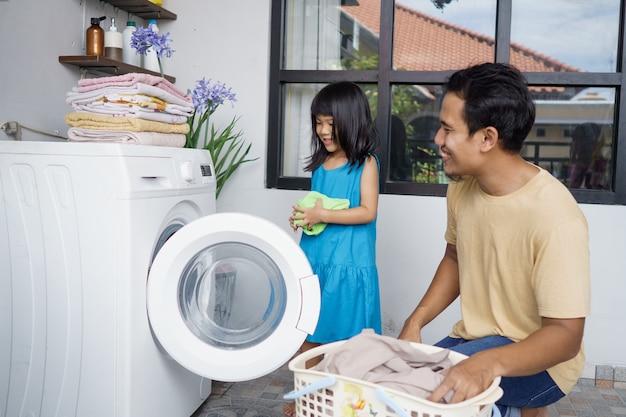 アジアの幸せな家族の男性父世帯主と子供娘が一緒に洗濯機で洗濯