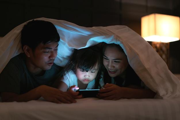 Азиатская счастливая семья смотрит фильм на смартфоне