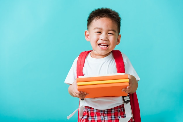 Asian happy funny little child boy smiling and laugh holding books