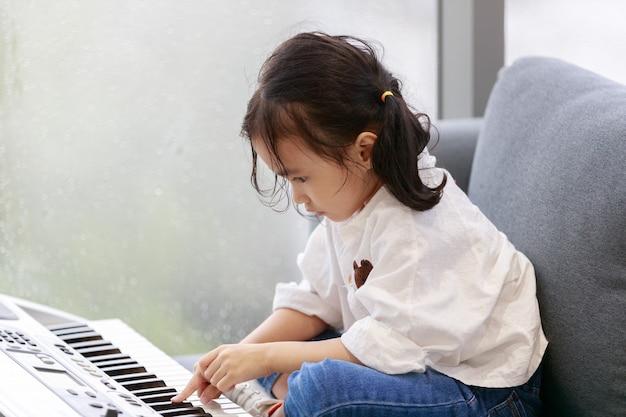 아시아의 행복한 소녀가 음악 연습실에서 피아노를 치고 있고, 바깥 분위기는 비가 내리고 있습니다. 유리에 물방울입니다. 개념 사랑스러운 학습 교육입니다.