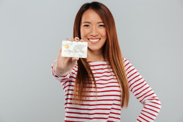Asian happy lady standing isolated holding credit card.