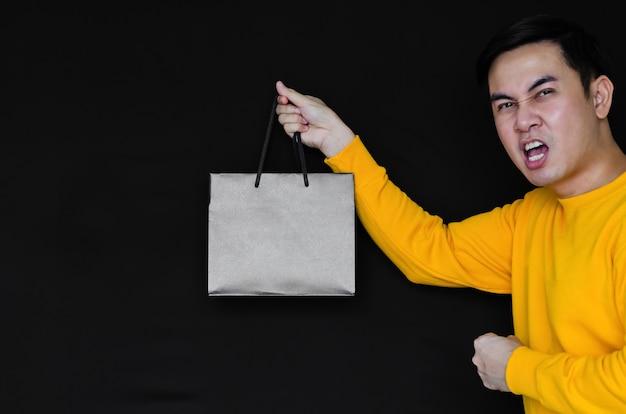 ブラックフライデーのコンセプトの暗い背景に買い物袋を保持しているアジアの幸せな男性。