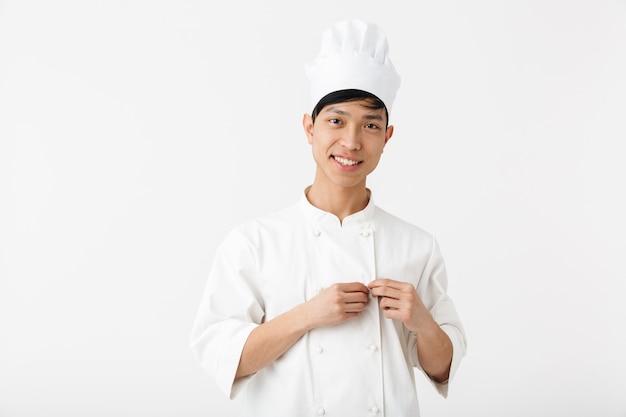 흰색 쿡 유니폼과 요리사의 모자에 아시아 행복 한 사람이 흰 벽 위에 절연 서있는 동안 카메라에 미소