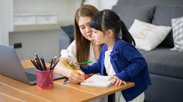 アジアの幸せなママと娘は自宅でインターネットを介してオンラインで勉強するためにラップトップを使用しています。隔離期間中のeラーニングの概念。