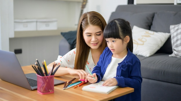 Азиатские счастливые мама и дочь используют ноутбук для онлайн-обучения через интернет дома. концепция электронного обучения во время карантина.