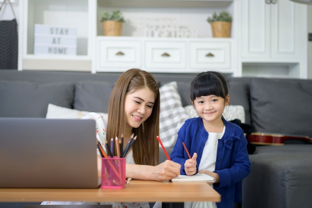 Asian happy mom and daughter are using laptop for studying online via internet at home. e-learning concept during quarantine time.