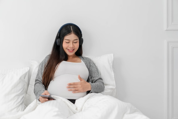 Asian happy pregnant woman is sitting on bed and and touching her belly and wear a headphone to listen the music