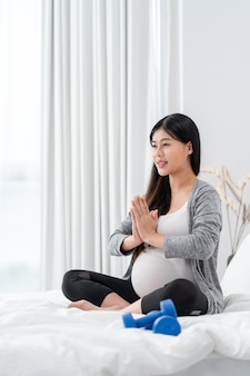 Asian happy pregnant woman is sitting and exercise on the bed  pregnancy