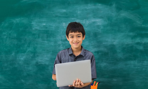 Asian happy school boy holding laptop on black board
