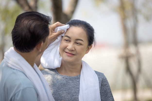屋外公園で走った後、妻の顔から汗を拭くアジアの幸せな年配のカップルの夫。