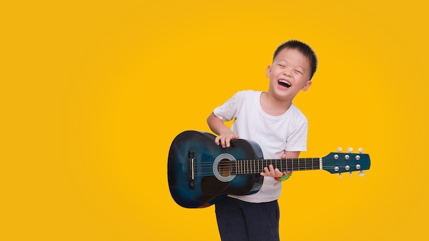 Asian happy smiling 5 years old boy having fun playing guitar isolated on colored background