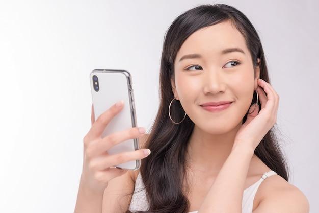 Азиатская счастливая женщина, используя смартфон