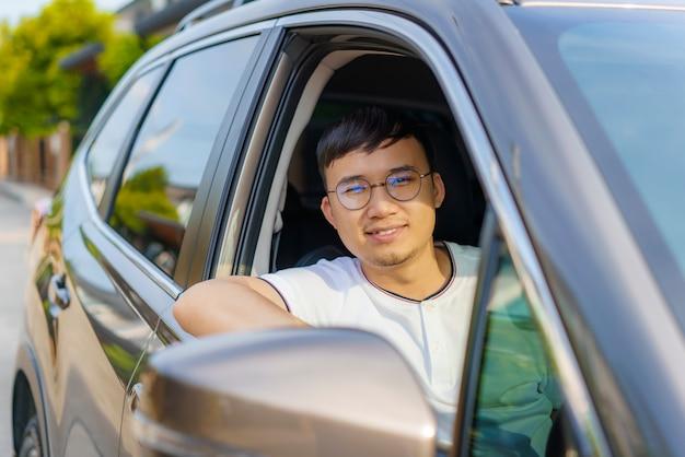 車を運転するアジアの幸せな若いハンサムな男