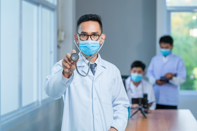 Азиатское здравоохранение и медицинская концепция. доктор медицины носить медицинскую маску со стетоскопом в руке и исследовательской группы в больнице новый нормальный фон баннера.