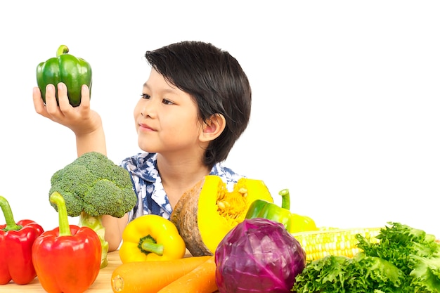 Asian healthy boy showing happy expression with variety fresh colorful vegetable