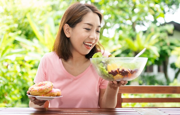 Asian healthy middle aged woman sitting and choose between a donut and a vegetable salad