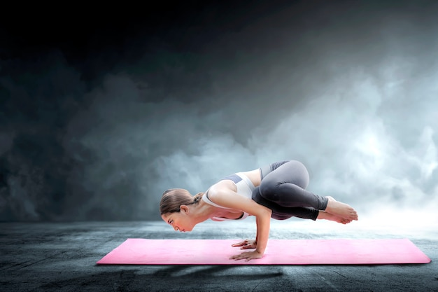 Asian healthy woman practicing yoga on the carpet at indoor