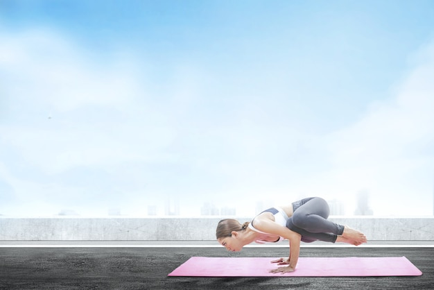 Asian healthy woman practicing yoga on the carpet at rooftop background