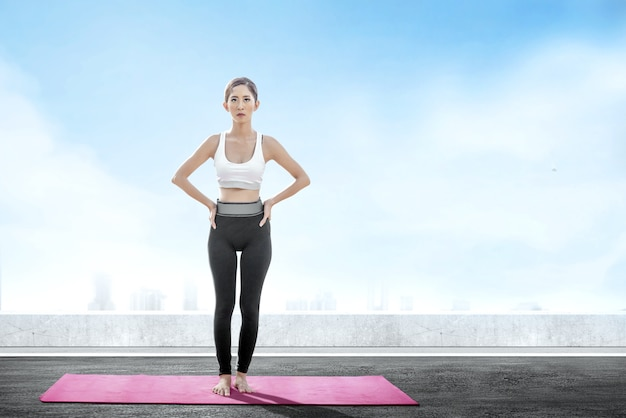 Asian healthy woman practicing yoga on the carpet at rooftop