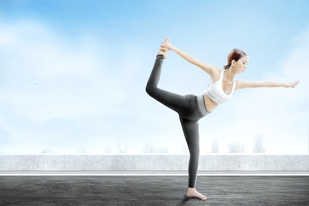 Asian healthy woman practicing yoga on the rooftop