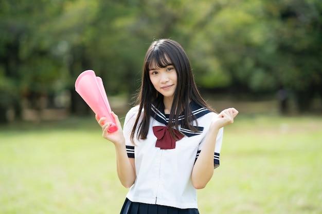 심장 모양의 확성기로 응원하는 아시아 고등학교 여학생 프리미엄 사진