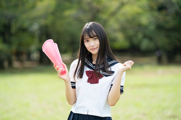 Asian high school female student cheering with a heart shaped megaphone