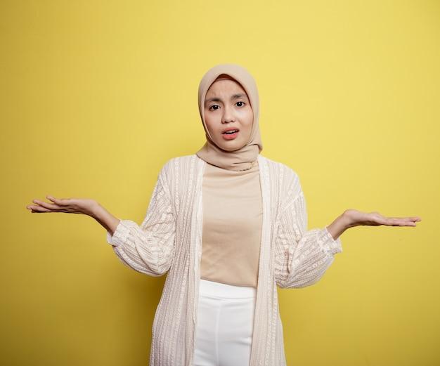 黄色の壁に隔離された手を開いて尋ねるアジアのヒジャーブの女性