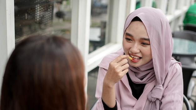 아시아 hijab 여자 친구와 함께 카페에서 감자 튀김을 먹는