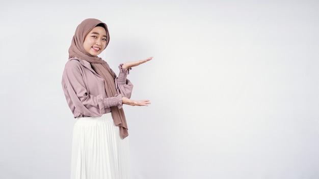 흰색 배경에 고립 웃고 왼쪽에 공백을 가리키는 아시아 히잡 여자