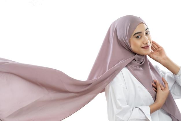 風になびく紫色のベールを身に着けているアジアのヒジャーブの女性