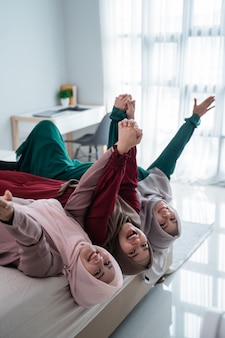 Азиатские хиджабские женщины и друзья ложатся и поднимают руки на кровати, весело проводя время вместе