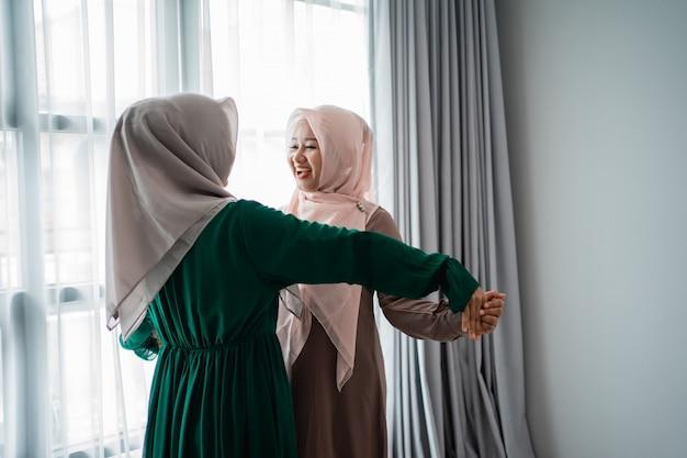 아시아 hijab 젊은 여자는 그들의 친구를 만나서 행복하다