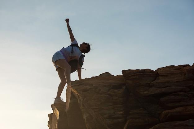 아시아 하이킹 여성은 일몰 동안 언덕 정상에 도달한 후 손을 듭니다. 보디빌딩과 건강한 라이프스타일을 위한 전문 여성 등반가. 야외 스포츠 활동의 승리 상징입니다.