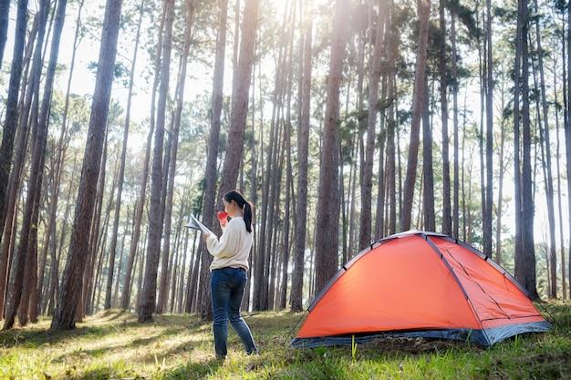 アジアのhipsterテントの外で日の出を楽しむかわいい十代の少女。森林にキャンプする。