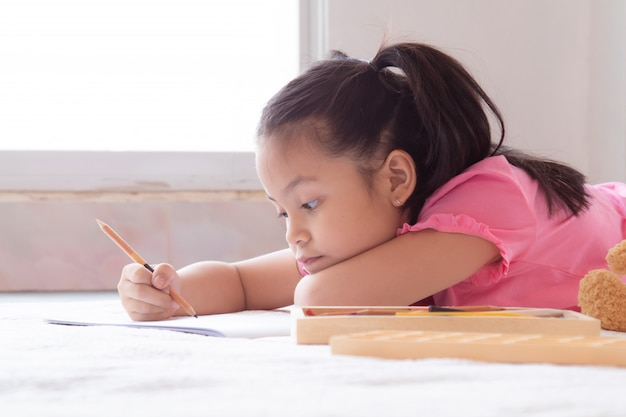 アジアの家庭学校のかわいい子供たちが床に横になって、色鉛筆で宿題を描く、幸せな陽気な女の子が学校に戻る前に検疫期間を描くことに集中して時間を費やした幸せ